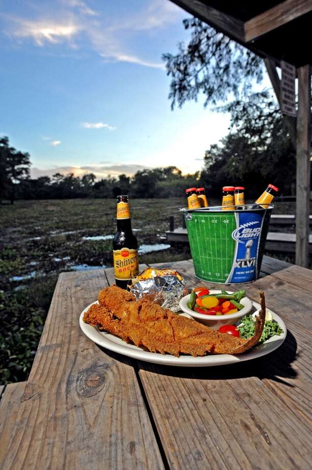 The sun sets at Pine Tree Lodge in LaBelle with their famous catfish platter and a bucket of beer. Photo taken Wednesday, September 19, 2013. Photo taken: Randy Edwards/The Enterprise Photo: Beaumont Enterprise