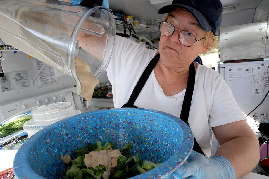 Katie Chenoweth prepares a caesar salad with homemade dressing at the Yellow Bird Farm food truck on Wednesday. The traveling treats and homemade meals can be spotted in front of D'Vine Wine on Calder. Photo taken Wednesday, September 11, 2013 Guiseppe Barranco/The Enterprise Photo: Guiseppe Barranco/The Enterprise