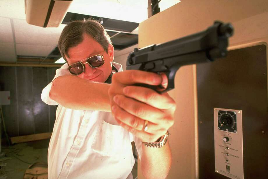 Novelist Tom Clancy is pictured with a Beretta during target practice in his private underground pistol range. The late author wrote many best-selling thrillers, many of which were made into movies. Look back at his books, films and video games. Photo: Ted Thai, Getty Images / Time Life Pictures