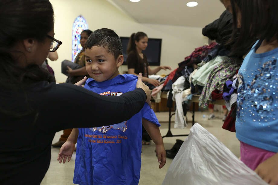 Daniela de León (left), a member of the Bexar County Young Tejano Democrats, helps Jonathan Kae, 3,  a refugee from Burma, find clothes to take home during the group's recent  Refugee Assistance Day. Photo: Lisa Krantz / San Antonio Express-News