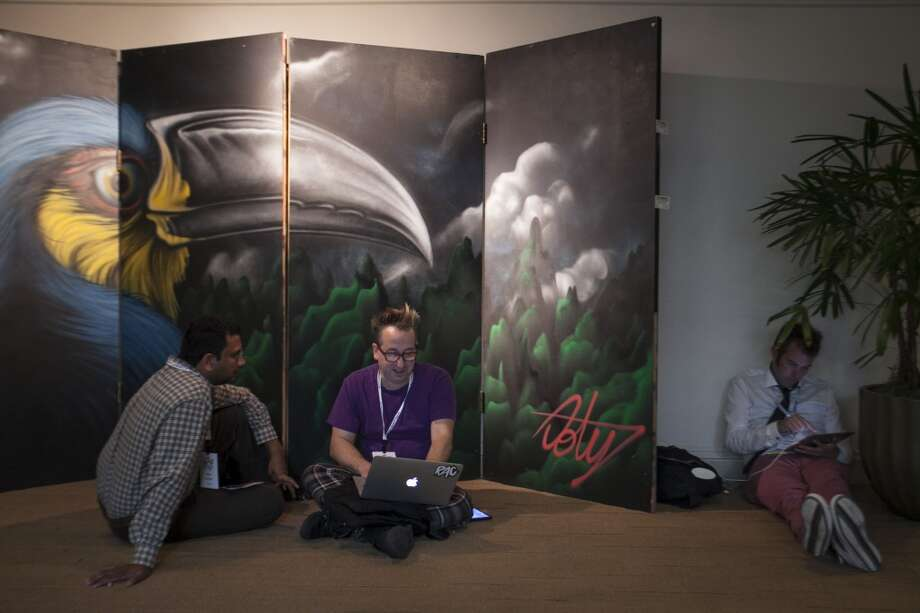 (Left to right) Chris Moulios Mihir Sarkar  and Stefan Aronsen  works on their labtops in front of a large mural at the SF Music Tech summit in San Francisco on October 1st 2013. in San Francisco on October 1st 2013. Photo: Special To The Chronicle