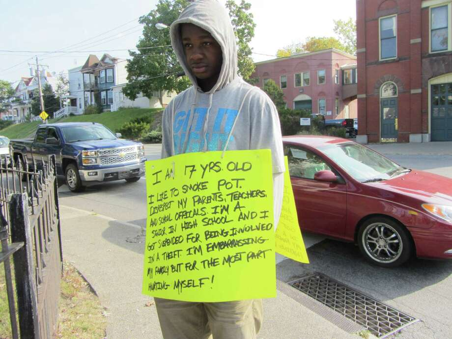 Rodney Green Jr., 17, of Speigletown, a senior at Lansingburgh High School, started wearing this placard as punishment for misbehaving. His father insisted that he wear the sign in busy areas. (Bob Gardinier / Times Union)