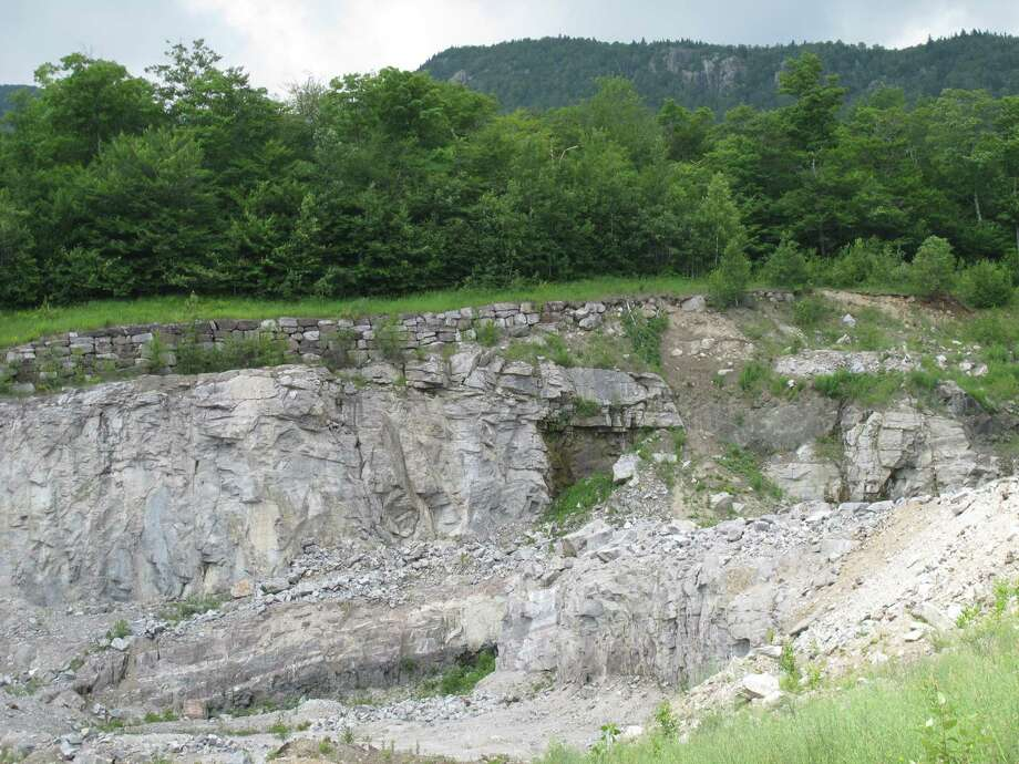 A wall of wollastonite in a pit mine in the Adirondacks is topped by a stone retaining wall beyond which lies 200 acres of constitutionally protected state land that the mining company, NYCO Minerals, wants to swap for 1,500 acres elsewhere so it can expand its mine. The land swap will go to NY voters on the November ballot. Photo taken Tuesday, July 9, 2013, in Lewis, N.Y. (AP Photo/Mary Esch) ORG XMIT: RPME102 ORG XMIT: MER2013071310584395 Photo: Mary Esch / AP