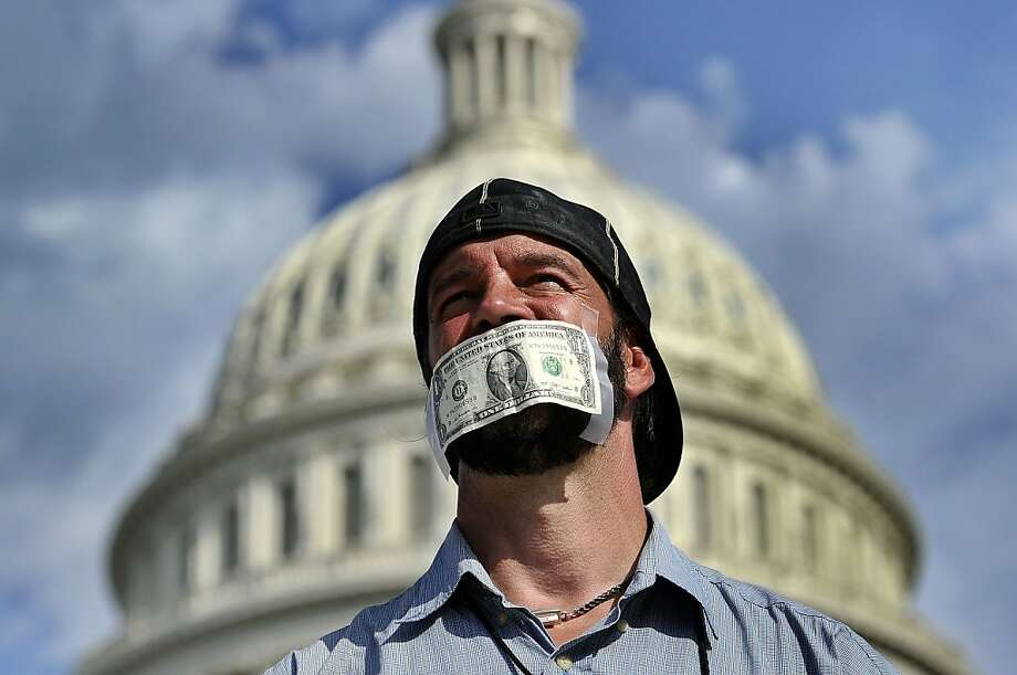 Shutdown gag: Money talks, but this guy can't because he has a dollar bill taped over his mouth during a rally against the 