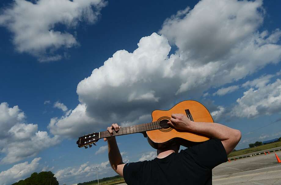 Honey, I just can't wait ... 'til you graduate ...James Kelvin plays his guitar behind his head in the   parking lot at Calhoun Community College in Decatur, Ala. He was waiting for his wife to finish a class. Photo: Gary Cosby Jr., Associated Press