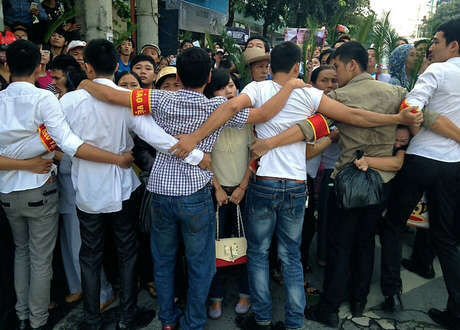 You can tell they're plainclothes cops by the red bands:Vietnamese plainclothes policemen form a human chain to prevent hundreds of protesters from approaching the People's Court in Hanoi, where Catholic activist lawyer Le Quoc Quan is being tried for tax evasion. Le has been in detention since December, when he blogged on a range of sensitive topics including civil rights, political pluralism and religious freedom. Photo: Cat Barton, AFP/Getty Images