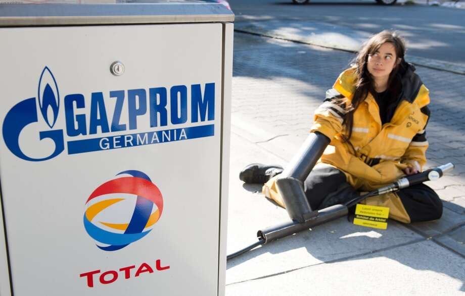 "A Greenpeace activist trusses herself to a gasoline pump at a Gazprom gas station in Berlin on October 2, 2013 to stage a protest against the imprisonment of environment protection campaigners in Russia. Russian investigators charged on October 2, 2013 five Greenpeace campaigners with piracy over an open-sea protest against Arctic oil drilling, the environmental group said, calling the move an ""outrage"". AFP PHOTO / DPA / MAURIZIO GAMBARINI / GERMANY OUTMAURIZIO GAMBARINI/AFP/Getty Images Photo: MAURIZIO GAMBARINI, AFP/Getty Images"