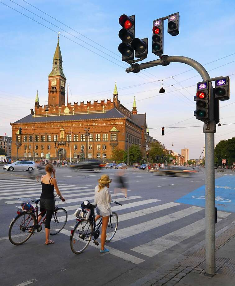 Bicyclists stop for a red light in front of the Town Hall in Copenhagen, which bills itself as the most bike-friendly city in the world. Photo: Shaun Egan, The Image Bank