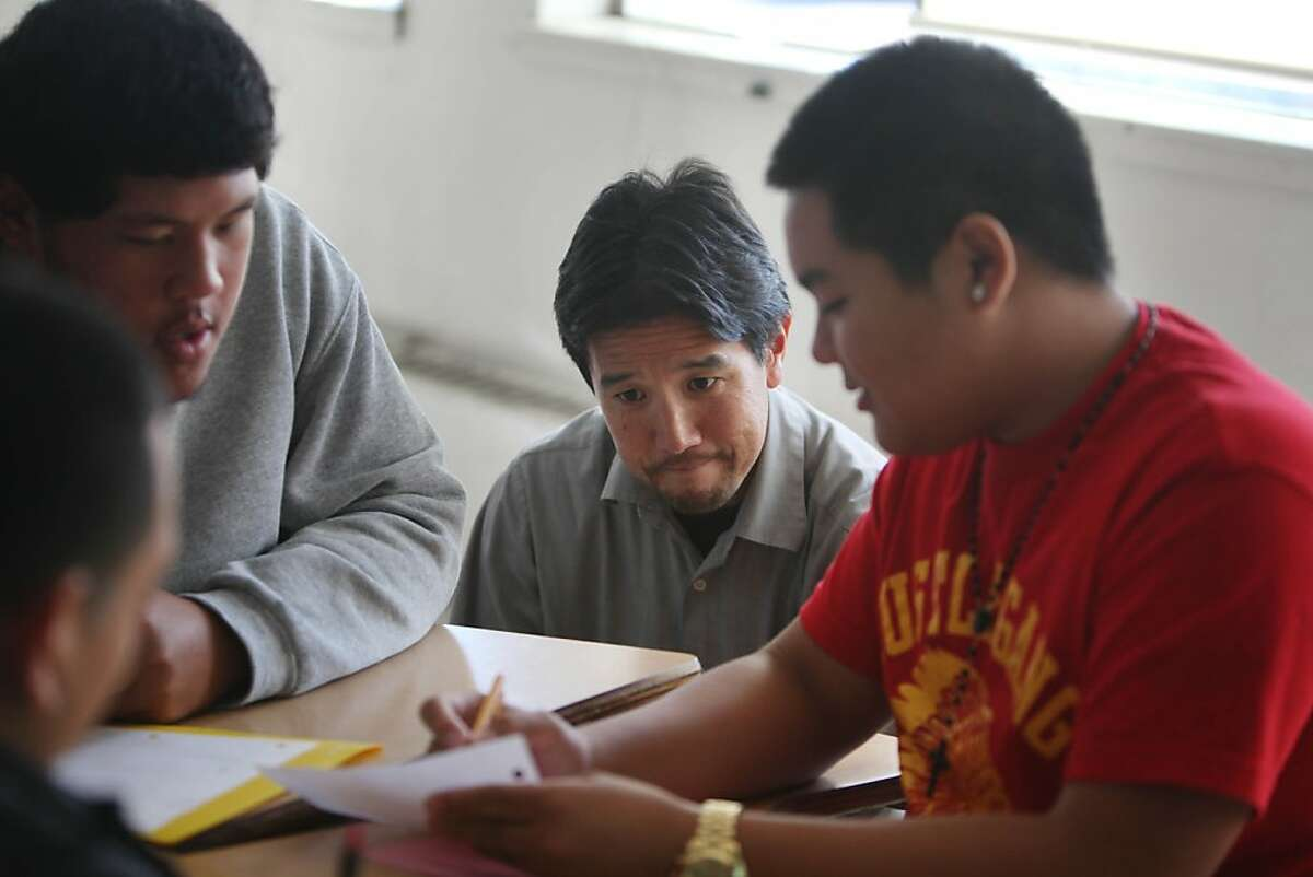Math instructor Dan Yamamoto (second from right), discusses class work with Juan Carlos Garcia (left), 16; Francis Sosoatu (second from left) and Ryan Sacdalan (right) during an Algebra II class at Phillip and Sala Burton Academic High School on Wednesday, October 2, 2013 in San Francisco, Calif.