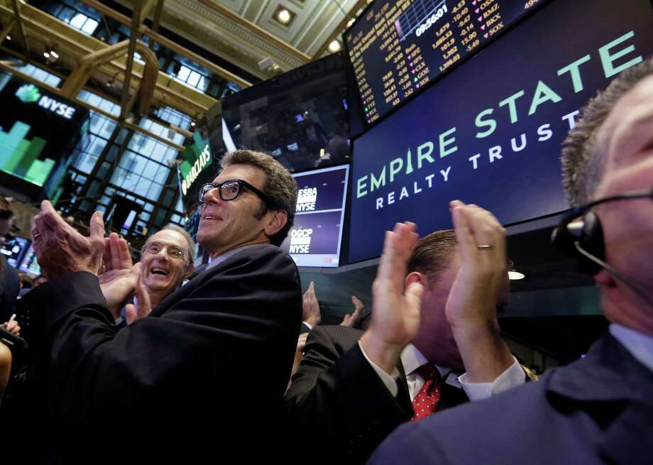 Chairman, CEO and President Anthony Malkin, foreground left, of Empire State Realty Trust, and Chairman Emeritus Peter Malkin, background left, applaud as their company's stock begins trading during its IPO on the floor of the New York Stock Exchange, Wednesday, Oct. 2, 2013. Empire State Realty Trust Inc., the real estate investment trust behind the Empire State Building, also manages other office buildings in the New York City area. (AP Photo/Richard Drew) ORG XMIT: NYRD101 Photo: Richard Drew / AP