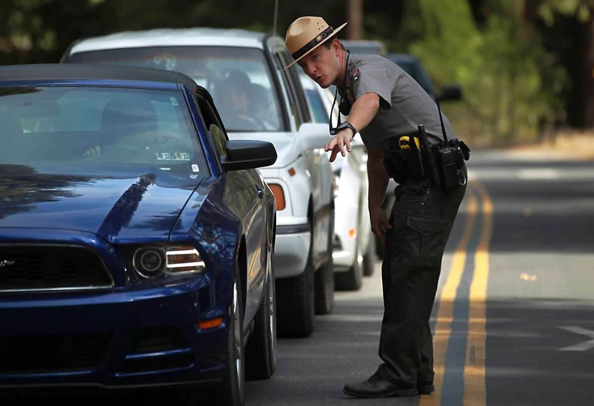 """U.S. Park Ranger Brendan Bonner informs outgoing vehicles that they will not be able to re-enter the park October 2, 2013 at Yosemite National Park. Due to the Federal Government shutdown, the park is now closed to outside visitors. All park-goers must leave by noon Thursday, after which most of the DNC Parks & Resorts workers will be placed on unpaid """"on-call"""" status."""