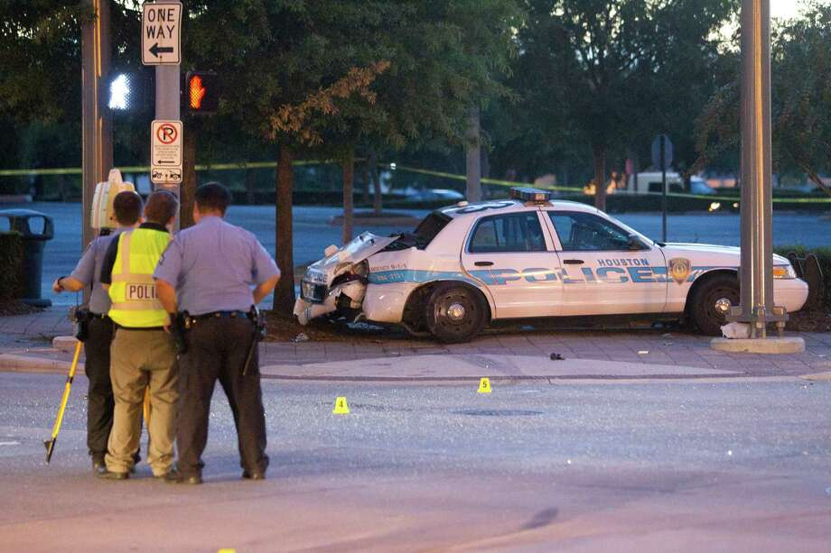 Police investigate a fatal accident involving a HPD police cruiser and a car. A woman, 21, who was in police custody, was killed. Photo: Johnny Hanson, Staff / Houston Chronicle