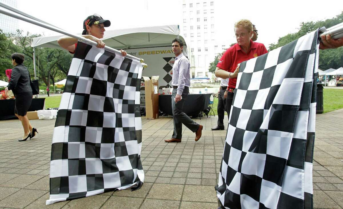 Shell employees Deidre Skaggs, left, and Cheryl Brown, right, roll up checkered flags after a Grand Prix of Houston event outside of City Hall Wednesday, Oct. 2, 2013, in Houston.
