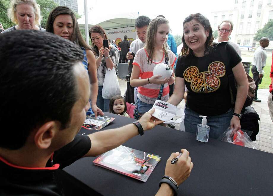 Indycar driver Helio Castroneves gives an autograph to Mechele Couger of Cypress during a Grand Prix of Houston event outside of City Hall Wednesday, Oct. 2, 2013, in Houston. Photo: Melissa Phillip, Houston Chronicle / © 2013  Houston Chronicle