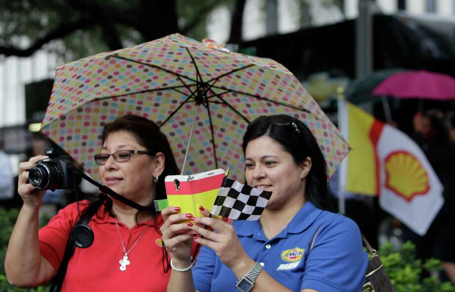 Shell employees Liz Rivera, left, and Roxanne Carranza, right, take photos during a Grand Prix of Houston event outside of City Hall Wednesday, Oct. 2, 2013, in Houston. Photo: Melissa Phillip, Houston Chronicle / © 2013  Houston Chronicle