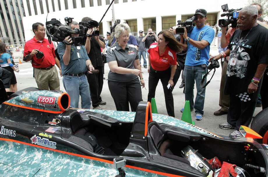 Mayor Annise Parker, center left, jokes with Selda Gunsel, center right, Shell vice president of global commercial technology, after Gunsel arrived in a two-seater IndyCar for a Grand Prix of Houston event outside of City Hall Wednesday, Oct. 2, 2013, in Houston. Photo: Melissa Phillip, Houston Chronicle / © 2013  Houston Chronicle