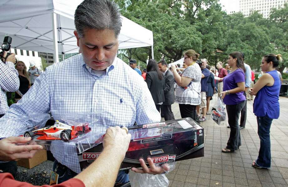 Frank Contreras puts an Indycar model back into box after having it autographed by Indycar driver Helio Castroneves during a Grand Prix of Houston event outside of City Hall Wednesday, Oct. 2, 2013, in Houston. Photo: Melissa Phillip, Houston Chronicle / © 2013  Houston Chronicle