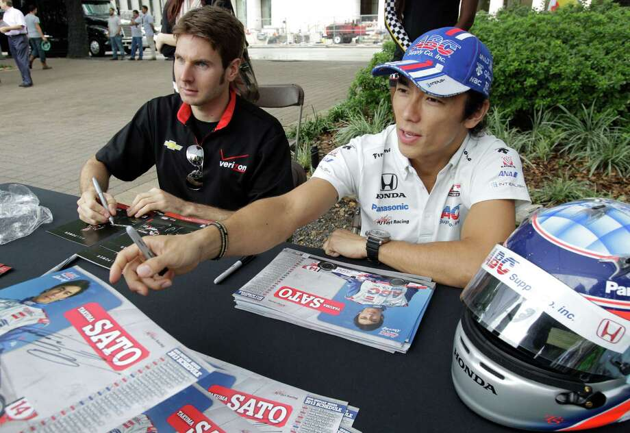 Indaycar driver Will Power, left, and Takuma Sato, right, give autographs during a Grand Prix of Houston event outside of City Hall Wednesday, Oct. 2, 2013, in Houston. Photo: Melissa Phillip, Houston Chronicle / © 2013  Houston Chronicle