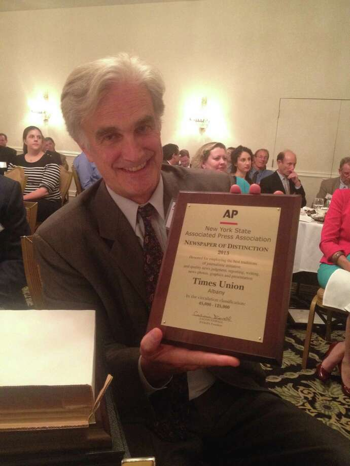 Rex Smith holds the Newspaper of Distinction Award at the Syracuse ceremony. (Will Waldron)