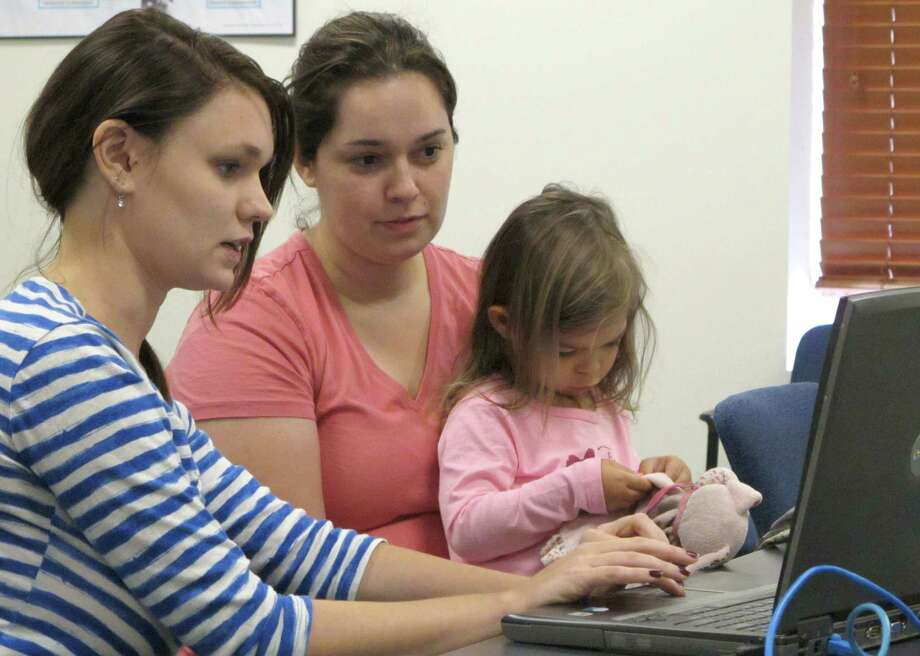 Debora Costa right,  tries to sign up for insurance coverage for her two children, including 2-year-old Victoria, Wednesday, Oct. 2, 2013, with help from Champaign Urbana Public Health District employee Alice Cronenberg in Champaign, Ill. Costa, who recently moved to Illinois from Brazil with her graduate-student husband and children, found after about 10 minutes that she didn't have all the information she would need to sign up. (AP Photo/David Mercer) ORG XMIT: RPDM101 Photo: David Mercer / AP