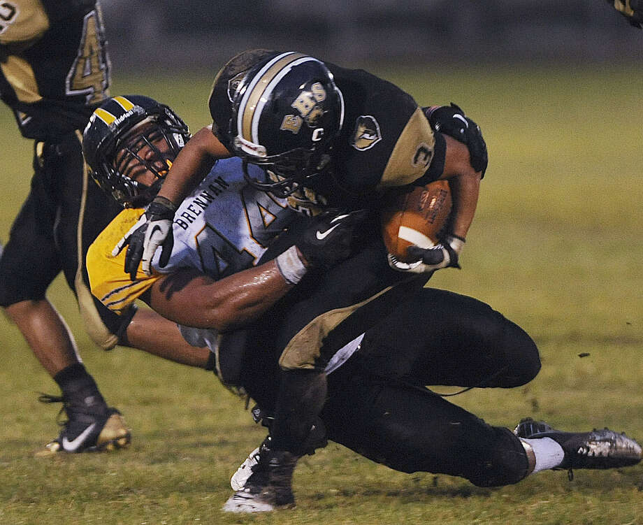 Grant Watanabe of Brennan wrestles Edison running back Andres Aguilar to the turf during their Week 4 meeting at the SAISD Sports Complex. Photo: Billy Calzada / San Antonio Express-News