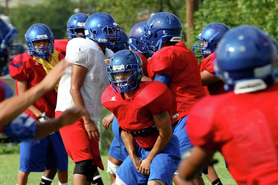 Memorial High School got its first on-field football victory since 2010 on Friday in a win against Pearsall. Head Coach Alex Guerra works with the team during practice on Thursday Sept. 5, 2013. Photo: San Antonio Express-News / ©2013 San Antonio Express-News