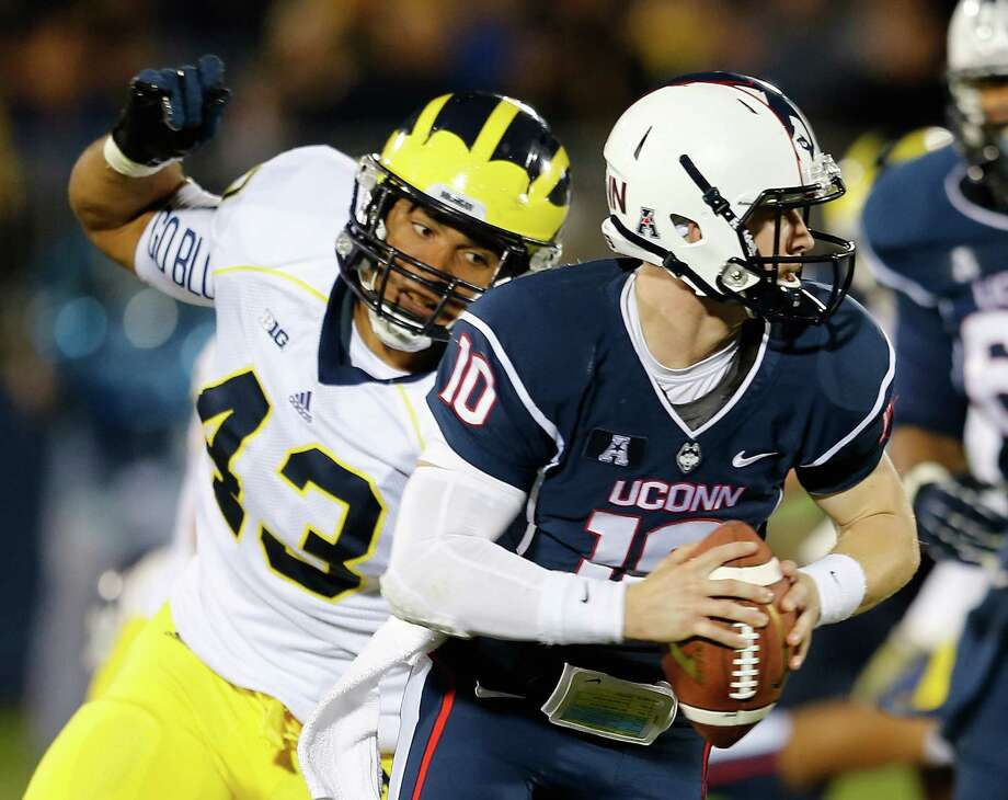 EAST HARTFORD, CT - SEPTEMBER 21: Chris Wormley #43 of the Michigan Wolverines  chases Chandler Whitmer #10 of the Connecticut Huskies in the second half at Rentschler Field on September 21, 2013 in East Hartford, Connecticut. Photo: Jim Rogash, Getty Images / 2013 Getty Images