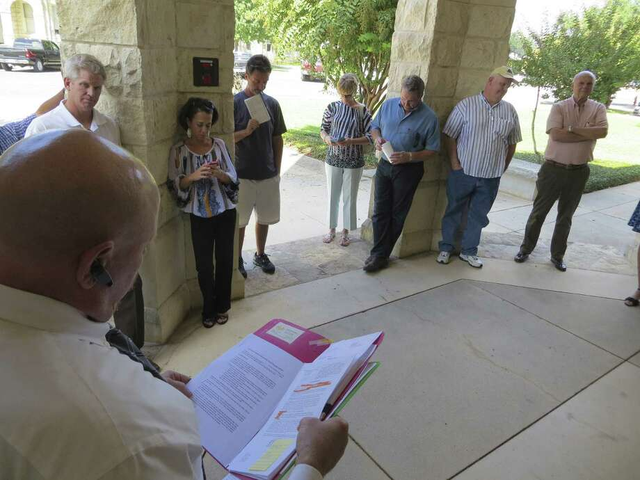 John Craig, substitute trustee, auctions off the former Esperanza development site outside Boerne on the porch of the Kendall County Courthouse on Tuesday. Craig submitted the only bid, of $14.5 million, on behalf of the lender, Credit Union Liquidity Services. Photo: Zeke MacCormack / San Antonio Express-News