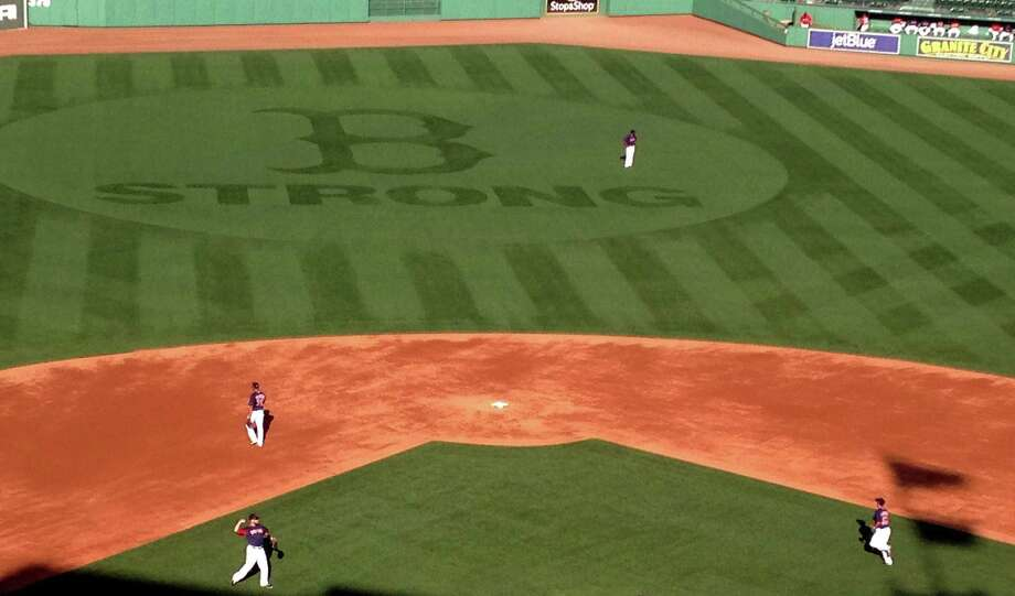 """A """"B Strong"""" logo adorns the grass in centerfield at Fenway Park while the Boston Red Sox work out on Wednesday, Oct., 2, 2013, in Boston. The Red Sox will pay tribute to victims of the Boston Marathon bombings when the AL division series opens Friday. The logo matches the patch the team has worn since the April 15 explosions. (AP Photo/Jimmy Golen) ORG XMIT: BX101 Photo: Jimmy Golen / AP"""
