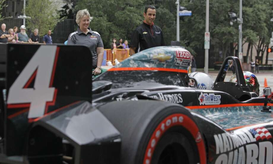 Mayor Annise Parker and Indycar driver Helio Castroneves watch after dropping the green flag for a two-seater IndyCart to arrive at City Hall Wednesday, Oct. 2, 2013, in Houston. During the event Mayor Annise Parker officially proclaimed the day as Shell and Pennzoil Grand Prix of Houston Day. ( Melissa Phillip / Houston Chronicle ) Photo: Melissa Phillip, Houston Chronicle