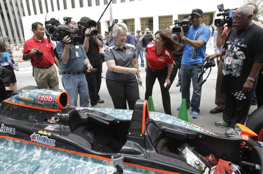 Mayor Annise Parker, center left, jokes with Selda Gunsel, center right, Shell vice president of global commercial technology, after Gunsel arrived in a two-seater IndyCar for a Grand Prix of Houston event outside of City Hall Wednesday, Oct. 2, 2013, in Houston. During the event Mayor Annise Parker officially proclaimed the day as Shell and Pennzoil Grand Prix of Houston Day. ( Melissa Phillip / Houston Chronicle ) Photo: Melissa Phillip, Houston Chronicle