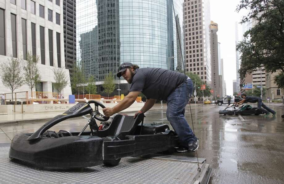 MSR Houston employees Shelby Sellers, left, and Scotty Gutelius, right, move go-karts onto a trailer after a Grand Prix of Houston event outside of City Hall Wednesday, Oct. 2, 2013, in Houston. Four Indycar drivers were scheduled to race a few laps in the go-karts, but rain cancelled the go-kart race. During the event Mayor Annise Parker officially proclaimed the day as Shell and Pennzoil Grand Prix of Houston Day. ( Melissa Phillip / Houston Chronicle ) Photo: Melissa Phillip, Houston Chronicle