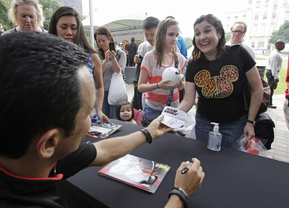 Indycar driver Helio Castroneves gives an autograph to Mechele Couger of Cypress during a Grand Prix of Houston event outside of City Hall Wednesday, Oct. 2, 2013, in Houston. During the event Mayor Annise Parker officially proclaimed the day as Shell and Pennzoil Grand Prix of Houston Day. ( Melissa Phillip / Houston Chronicle ) Photo: Melissa Phillip, Houston Chronicle