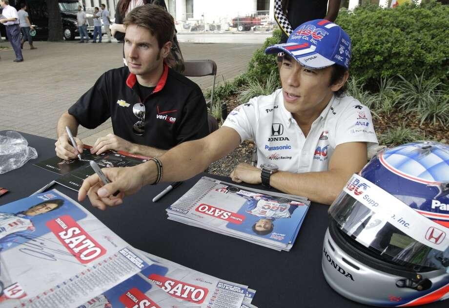 Indaycar driver Will Power, left, and Takuma Sato, right, give autographs during a Grand Prix of Houston event outside of City Hall Wednesday, Oct. 2, 2013, in Houston. During the event Mayor Annise Parker officially proclaimed the day as Shell and Pennzoil Grand Prix of Houston Day. ( Melissa Phillip / Houston Chronicle ) Photo: Melissa Phillip, Houston Chronicle