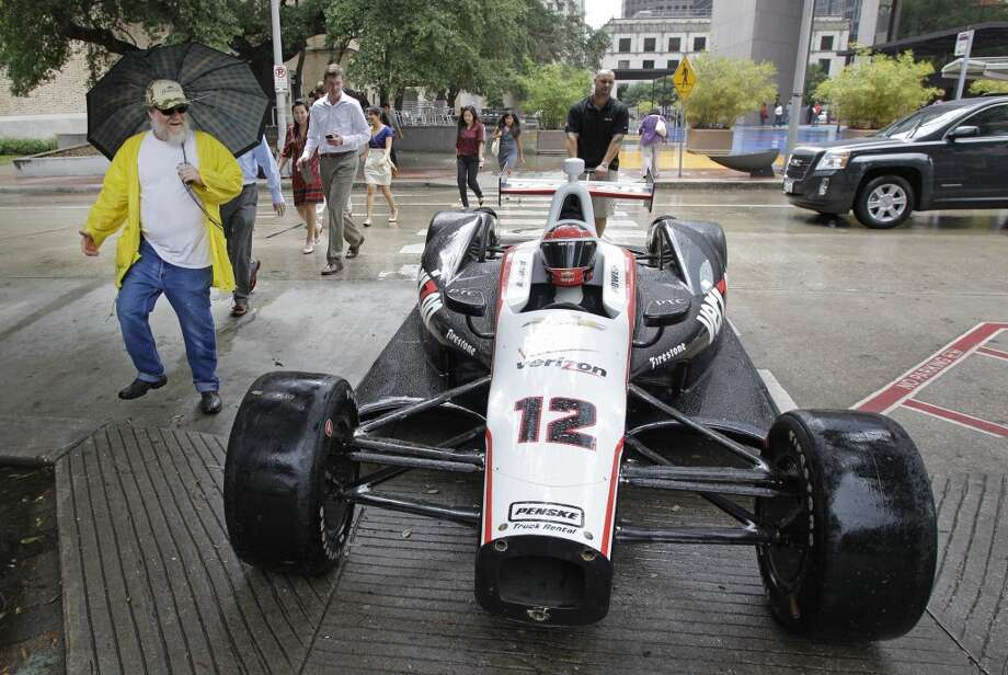 Pedestrians walk through crosswalk along McKinney St. as Bill Puckett of Greensboro, NC pulls a Will Power's Indycar show car to trailer  after it was displayed at a Grand Prix of Houston event outside of City Hall Wednesday, Oct. 2, 2013, in Houston. During the event Mayor Annise Parker officially proclaimed the day as Shell and Pennzoil Grand Prix of Houston Day. ( Melissa Phillip / Houston Chronicle ) Photo: Melissa Phillip, Houston Chronicle