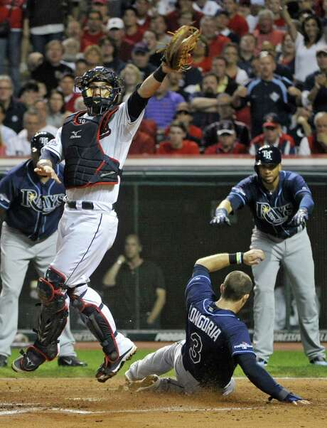 Indians catcher Yan Gomes jumps to reach a high throw as the Rays' Evan Longoria slides into home with some guidance from teammate James Loney (right) in the fourth inning of Tampa Bay's win in Cleveland. Photo: Phil Long / Associated Press
