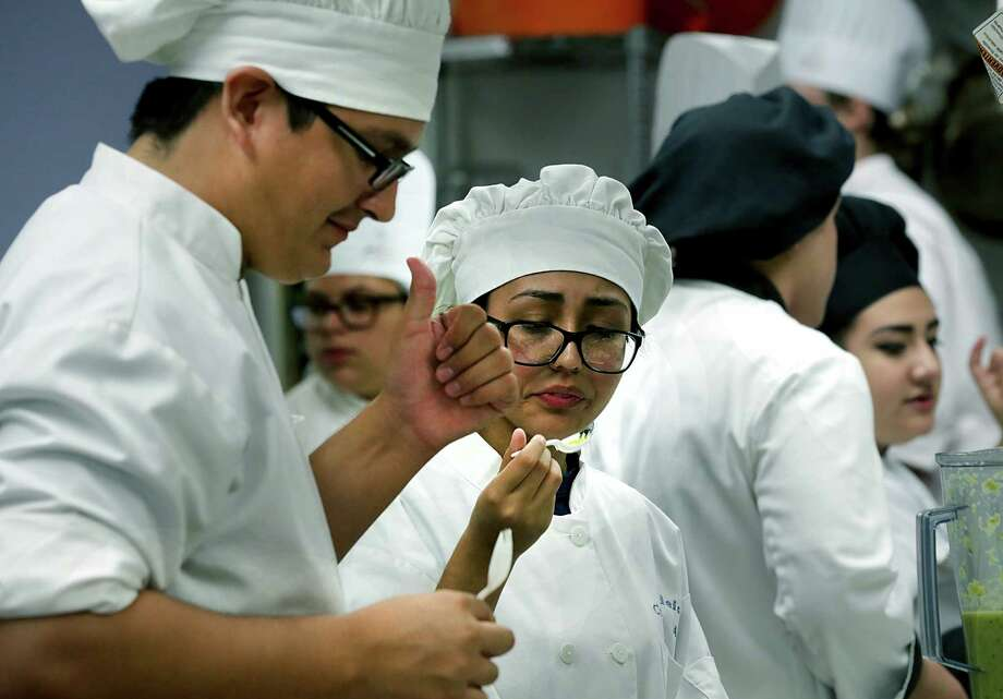 Dallas Bravo, left, of Brandeis High School, gives a thumbs up to his partner Alexis Hernandez, center, as she tastes their entry in the St. Philip's College Best Tasting Salsa Scholarship Competition on Wednesday, Oct. 2, 2013. Seven teams from area high schools participated in the event, with scholarship money going to first, second and third places. Photo: BOB OWEN, San Antonio Express-News / © 2012 San Antonio Express-News