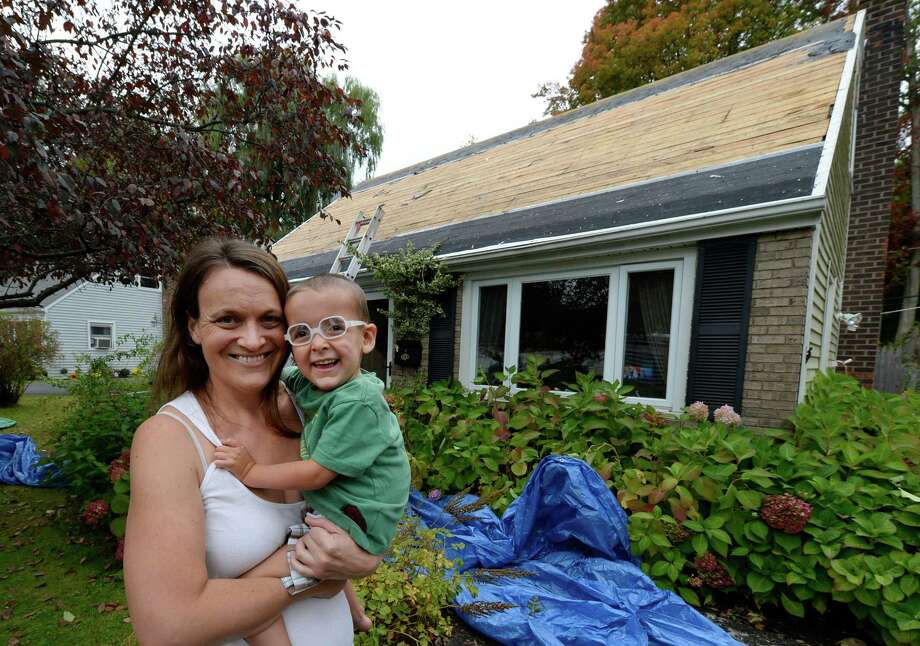 Stephanie Siciliano holds two year old Logan as work continues on the roof of their house Wednesday afternoon Oct. 2, 2013,  in Latham, N.Y.  Volunteers from the Albany County Corrections Children's Foundation are installing the new roof.        (Skip Dickstein / Times Union) Photo: Skip Dickstein