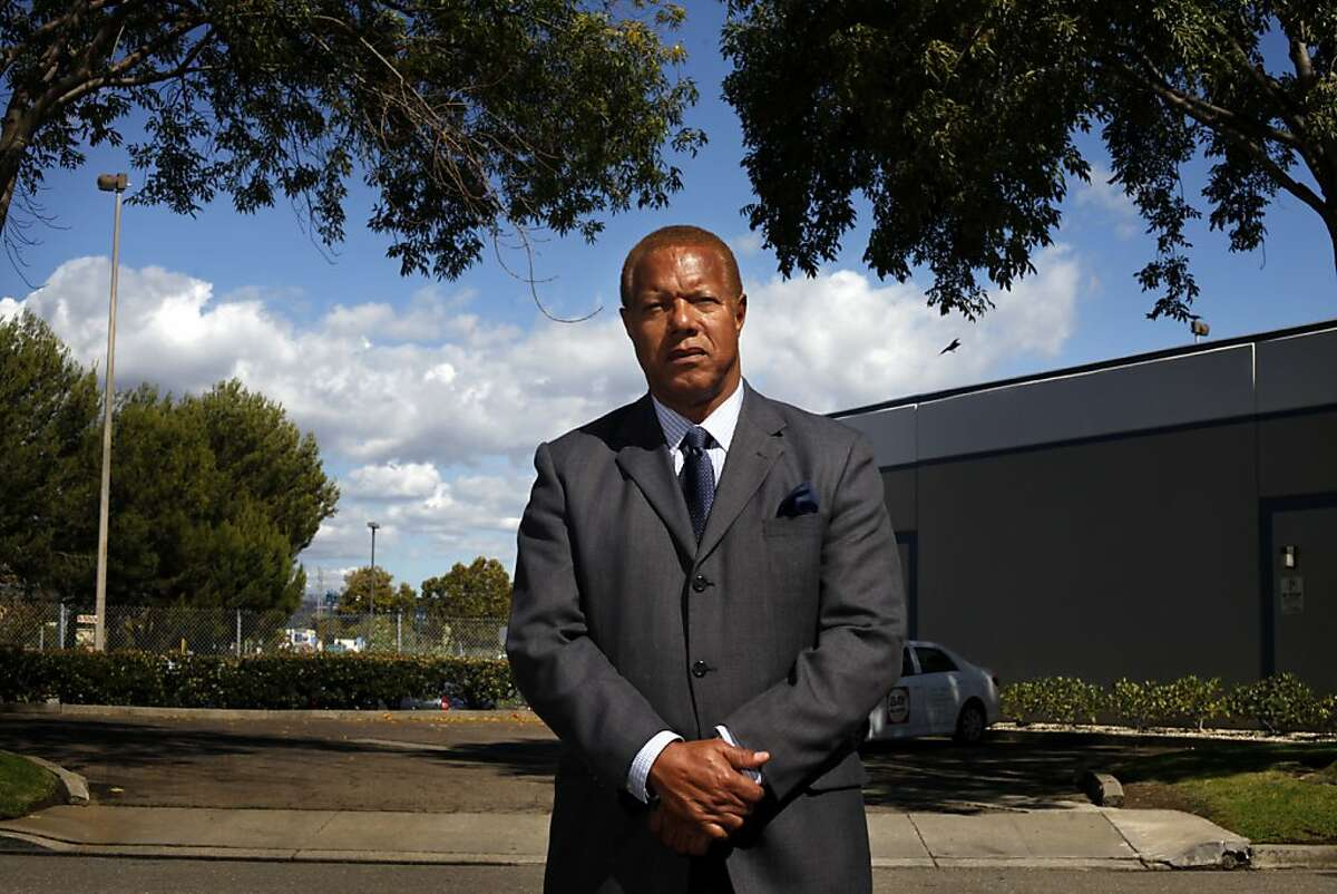 """Reverend Daniel Buford of Allen Temple Baptist Church, who is opposed to the Emeryville crematorium being moved to Oakland, stands in front of it's new home, Wednesday September 25, 2013, in Oakland, Calif. """" This is supposed to be the biggest crematorium in the West coast, burning over 3,000 bodies a year,"""" said Buford."""