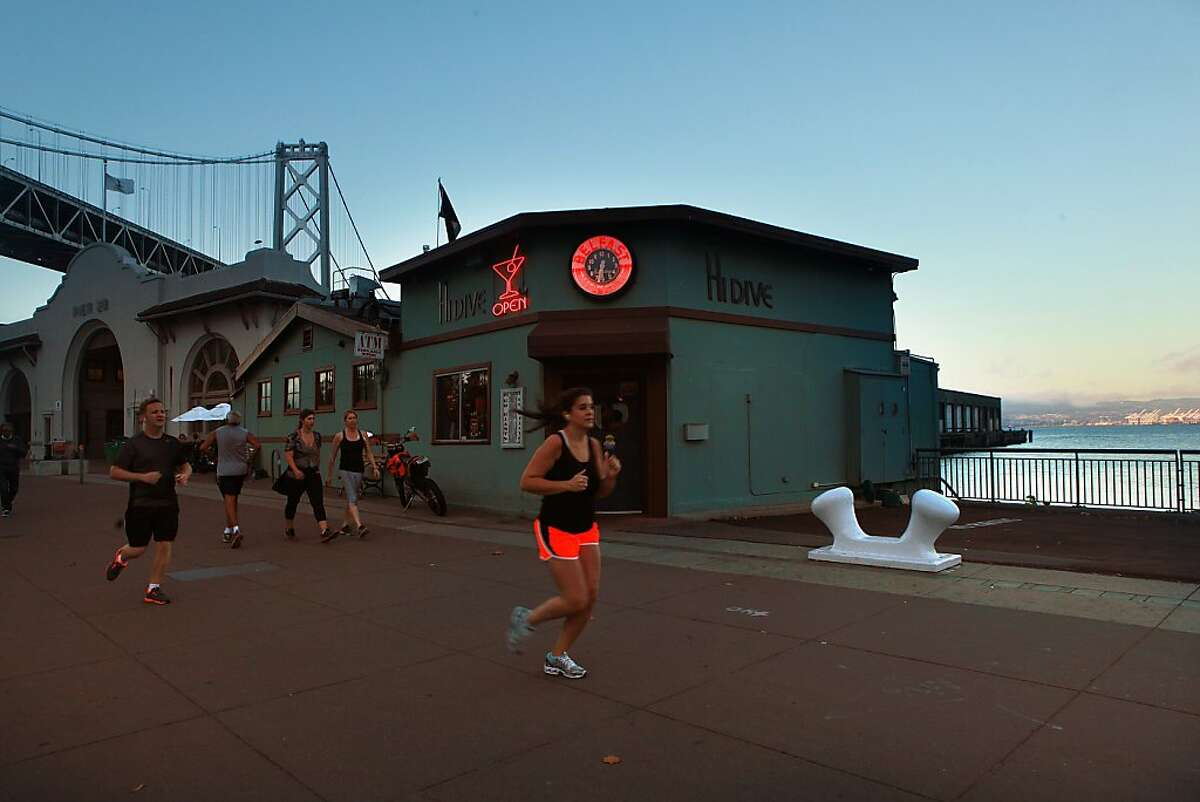 Runners pass by Hi Dive in San Francisco, California, on Wednesday, October 2, 2013.
