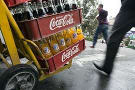 A worker pushes a hand truck with Coca-Cola products while making deliveries in Mexico City, Mexico, on Thursday, Sept. 5, 2013. Coca-Cola Femsa SAB, a bottler and distributor of Coca-Cola products in Mexico, agreed to buy Brazil's Spaipa SA Industria Brasileira de Bebidas in a cash deal with a total transaction value of $1.86 billion. Photographer: Susana Gonzalez/Bloomberg