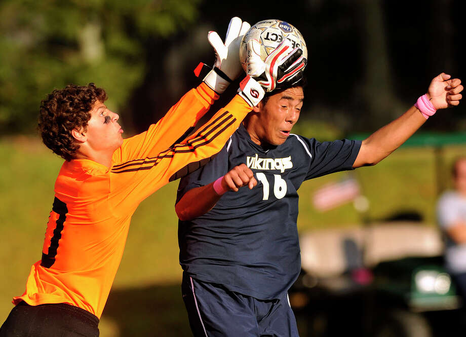 King's Danny Roca challenges Hopkins goalie Philip Geanakoplos in the air during their game at King school in Stamford, Conn., on Wednesday, Oct. 2, 2013. King school won, 4-0. Photo: Jason Rearick / Stamford Advocate