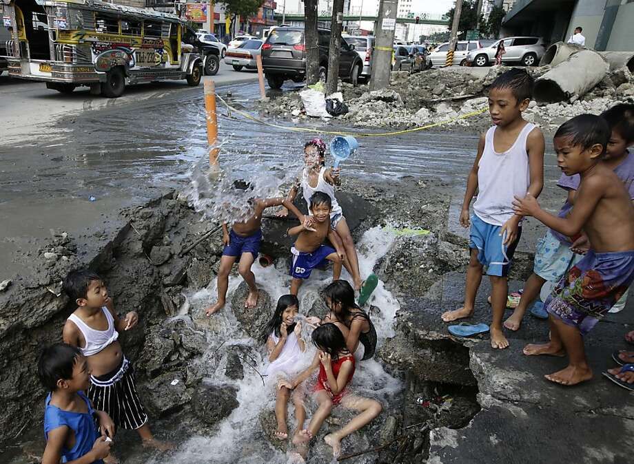 Decaying infrastructure is so much fun:Filipino kids take advantage of a broken water line in suburban Quezon city northeast of Manila. Photo: Bullit Marquez, Associated Press