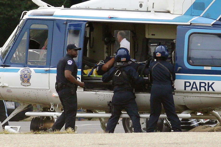 A U.S. Park Police helicopter is loaded on the Mall in Washington, Thursday, Oct. 3, 2013, with a victim from a shooting. Police say the U.S. Capitol has been put on a security lockdown amid reports of possible shots fired outside the building. Photo: AP