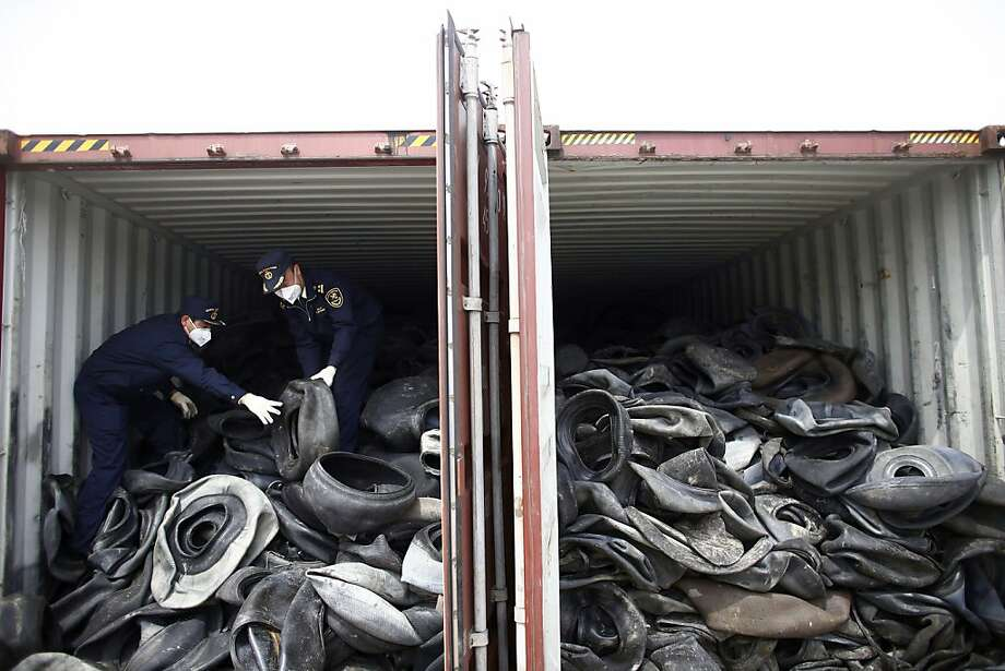 Chinese customs officials check a container of illegally imported used tires in Shanghai. The government's new program Green Fence is cracking down on foreign waste imports. Photo: Associated Press