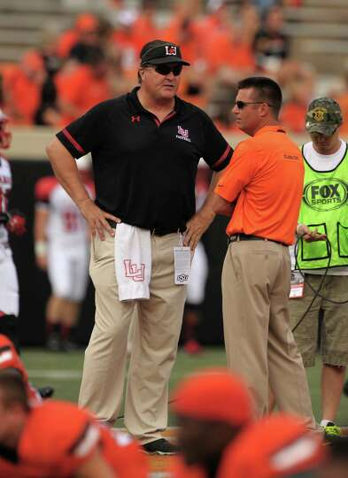 Lamar head coach Ray Woodard (left) and Oklahoma State head coach Mike Gundy (right) talk before a g