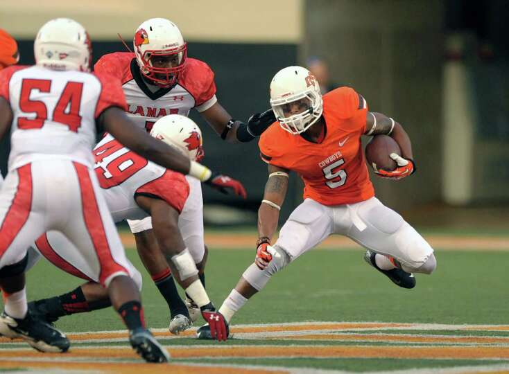 Oklahoma state wide receiver Josh Stewart (right) evades Lamar defenders during the first half of an
