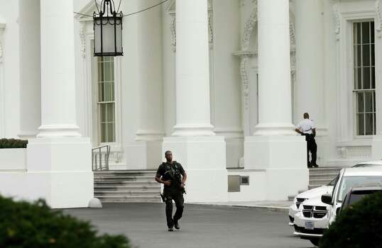 A member of the Secret Service Counter Assault team walks past the entrance of the White House in Washington, Thursday, Oct. 3, 2013, after reports of shot being fired on Capitol Hill. Photo: AP