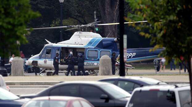 A U.S. Park Police helicopter is loaded on the Mall in Washington, Thursday, Oct. 3, 2013, with a victim from a shooting. Police say the U.S. Capitol has been put on a security lockdown amid reports of possible shots fired outside the building.  (AP Photo/Alex Brandon) Photo: Associated Press