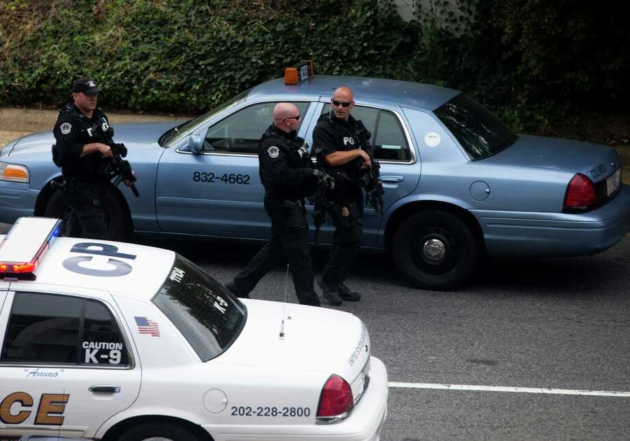 Capitol Hill police officers respond to a shooting on Capitol Hill in Washington, Thursday, Oct. 3, 2013. Police say the U.S. Capitol has been put on a security lockdown amid reports of possible shots fired outside the building.  (AP Photo/ Evan Vucci) Photo: Associated Press